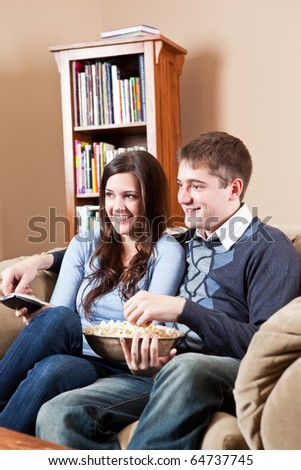 A couple sitting on sofa and watching television