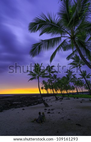 "A couple sitting on the beach under coconut palm trees, near lava rock tide pools on The Big Island, Hawaii. / ""Beach sunset couple"""