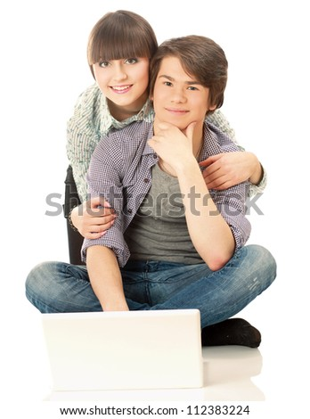 A couple sitting on the floor behind a laptop, isolated on white