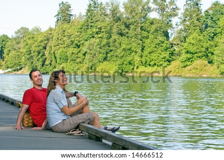 A couple, sitting together on a dock, with their feet dangling over into the water, laughing. - horizontally framed