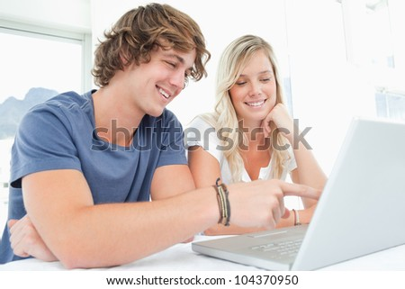 A couple sitting together smile as they look at the laptop - stock photo