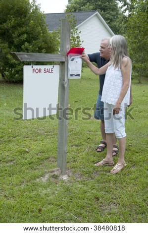 A couple takes and information sheet in front of a home they might purchase. - stock photo