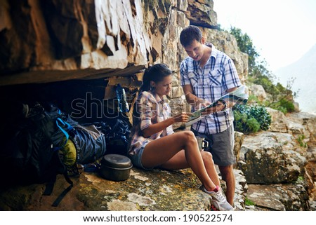 A couple taking a break from their hiking trail and looking at a map - stock photo
