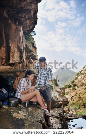 A couple taking a break from their hiking trail and looking at a map with copyspace - stock photo