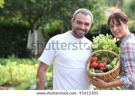 A couple taking care of their vegetable garden. - stock photo
