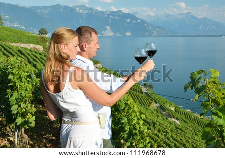 A couple tasting wine among vineyards in Lavaux, Switzerland - stock photo