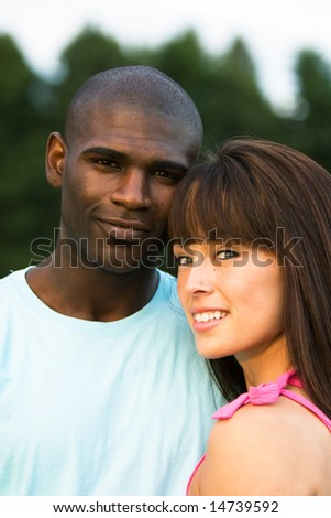 A couple together, smile at the camera while outdoors. - vertically framed