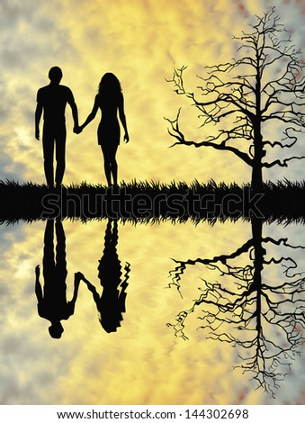 a couple walking at sunset with reflection - stock photo