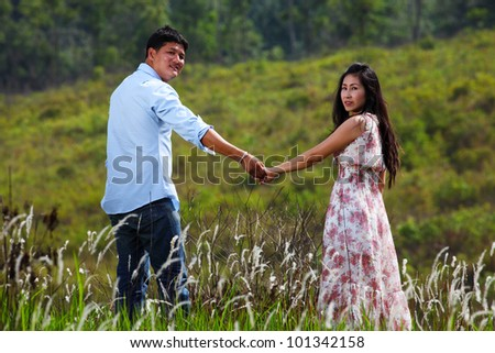 A Couple Walking Through A Grassland, holding hands - stock photo