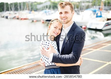 A couple walks along the pier boats at sea in sunny weather