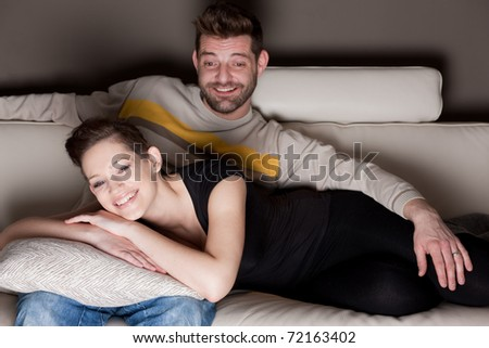 A couple watching TV on a sofa. - stock photo