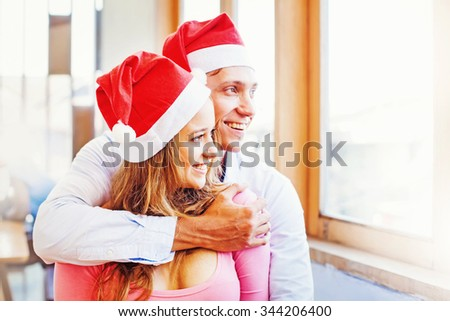 a couple wearing christmas santa red hats hugging and looking to the window. Focus on a woman - stock photo