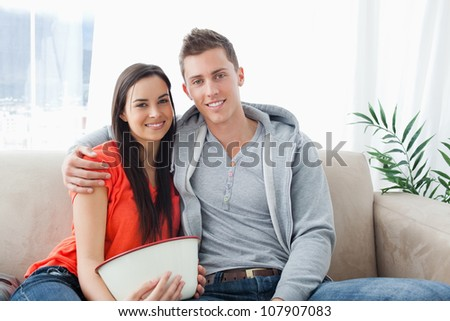 A couple with a bowl wit together on the couch as they look into the camera