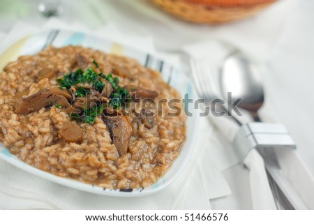 A course of Risotto with artichokes on a white prepared table. Shallow depth of field on cut artichokes and rice - stock photo