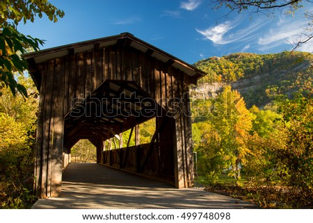 A covered bridge in the mountains in early autumn.