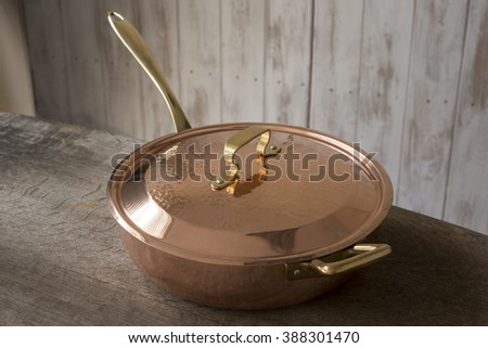 A covered copper skillet place on edge of wooden countertop. - stock photo