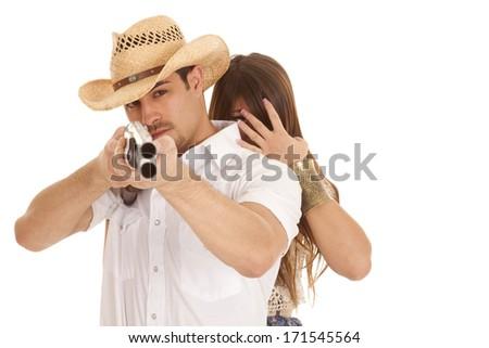 a cowboy aiming a gun while his woman is behind him hiding her eyes. - stock photo