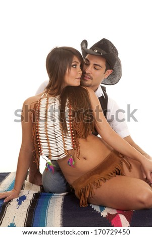 A cowboy and Indian couple are sitting together on a blanket about to kiss. - stock photo