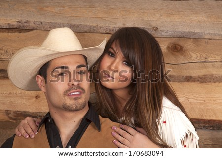 A cowboy and Indian couple are smiling in front of a wooden background. - stock photo