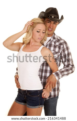 A cowboy behind his woman with her back up to him. - stock photo