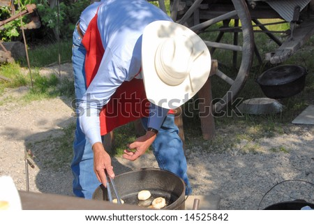 A Cowboy Cooking Biscuits in a Dutch Oven