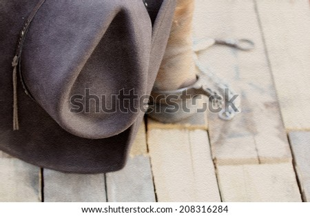 A cowboy hat, boots, spurs and a bit in a rustic textured background. - stock photo