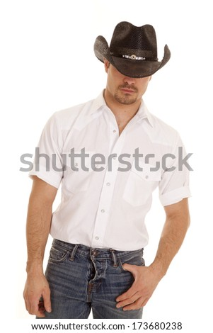 a cowboy hiding his eyes with his hat. - stock photo