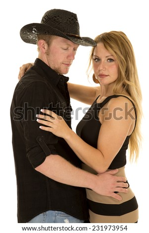 a cowboy holding his woman close looking to the side. - stock photo