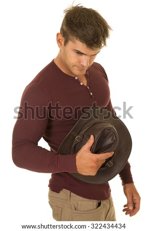 A cowboy holding on to his hat looking down. - stock photo