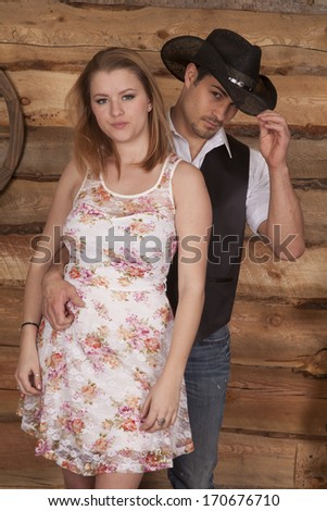 A cowboy holding on to his woman, he is touching the brim of his cowboy hat. - stock photo