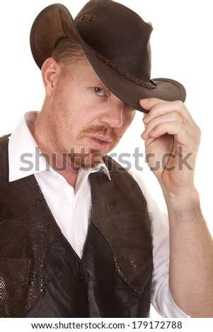 A cowboy in a vest and a hat close looks serious. - stock photo