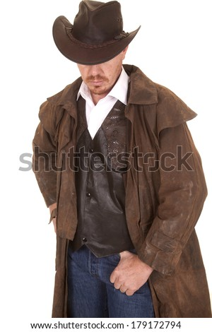 A cowboy in a vest and leather duster and hat looking down. - stock photo