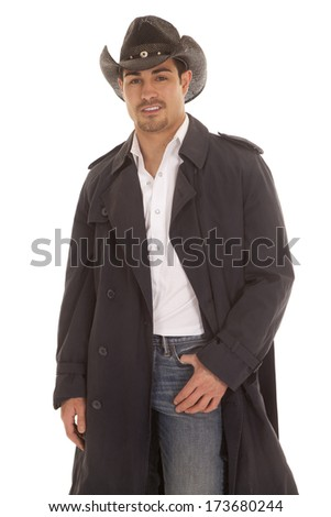 A cowboy in his coat with a half of a smile on his face. - stock photo