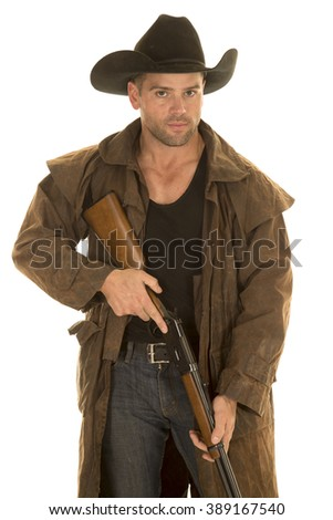 A cowboy in his duster holding his rifle with a serious expression on his face.