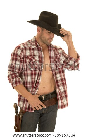 A cowboy in his plaid shirt open and showing off his chest, with his pistol on his hip. - stock photo