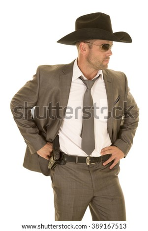 A cowboy in his suit and hat showing off his pistol on his hip.