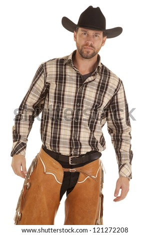 A cowboy in his western chaps and plaid shirt with his black hat on his head looking serious. - stock photo