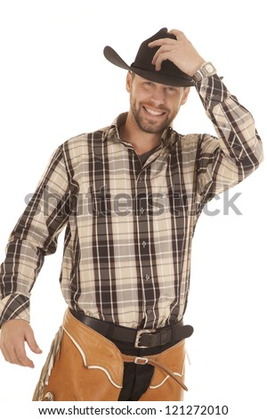 a cowboy in his western gear with a smile on his face holding on to his hat. - stock photo