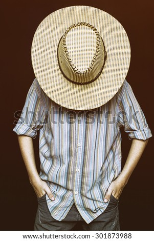 A cowboy is hiding behind his hat - stock photo