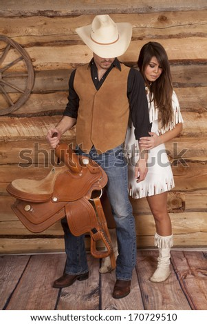 A cowboy is holding a saddle and is looking down with an Indian. - stock photo