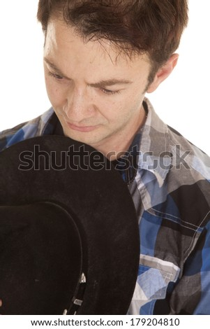 A cowboy is holding his hat against his body looking down. - stock photo
