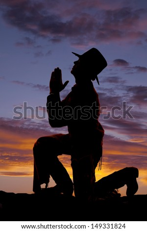 A cowboy is kneeling to pray silhouetted. - stock photo
