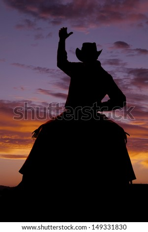 A cowboy is on a horse bucking in the sunset. - stock photo