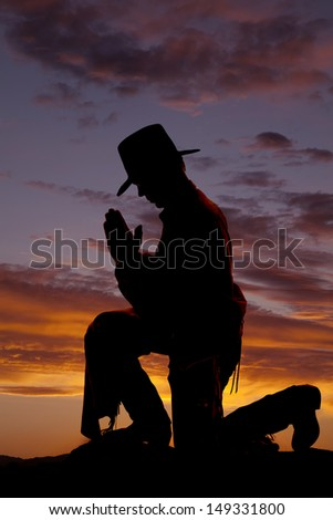 A cowboy is silhouetted and kneeling to pray. - stock photo