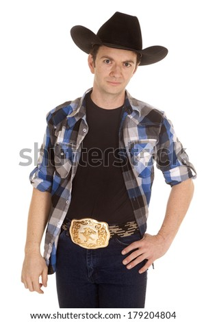 A cowboy is standing with his hand on his hip wearing a big black hat. - stock photo