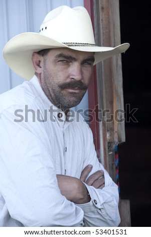 A cowboy leans against a door frame with his arms crossed. - stock photo