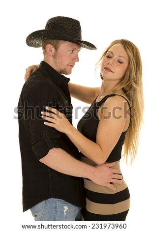 a cowboy looking at his woman while she has her eyes closed. - stock photo