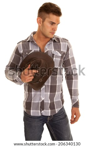 a cowboy looking down holding onto his hat. - stock photo