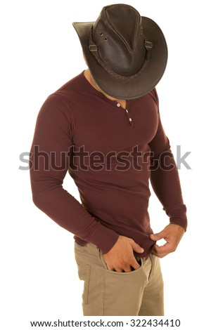 A cowboy looking down in his fit tight shirt.