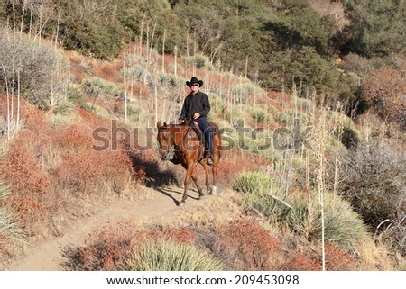 A cowboy on a high desert mountain trail. - stock photo